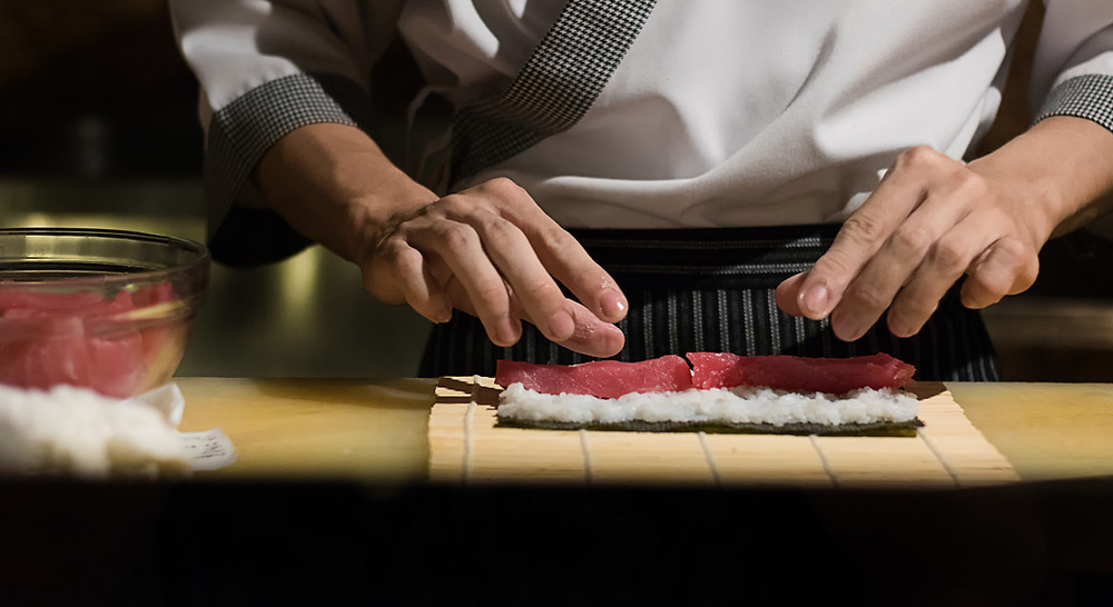 Chef (without face) preparing sushi roll