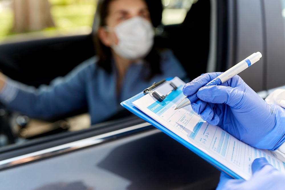 Woman in car is wearing a mask while communicating with the doctor who writes down diagnosis
