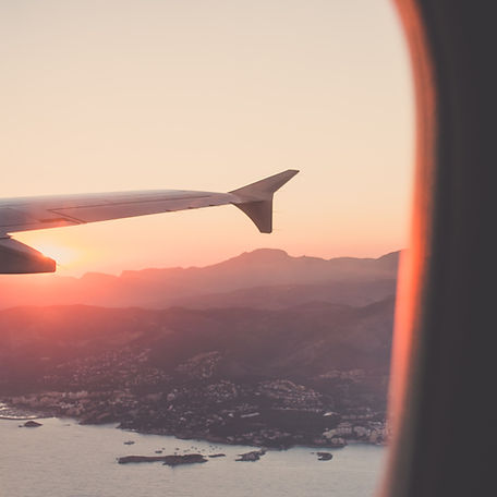 Sunset over the Mountains through a window of an aeroplane