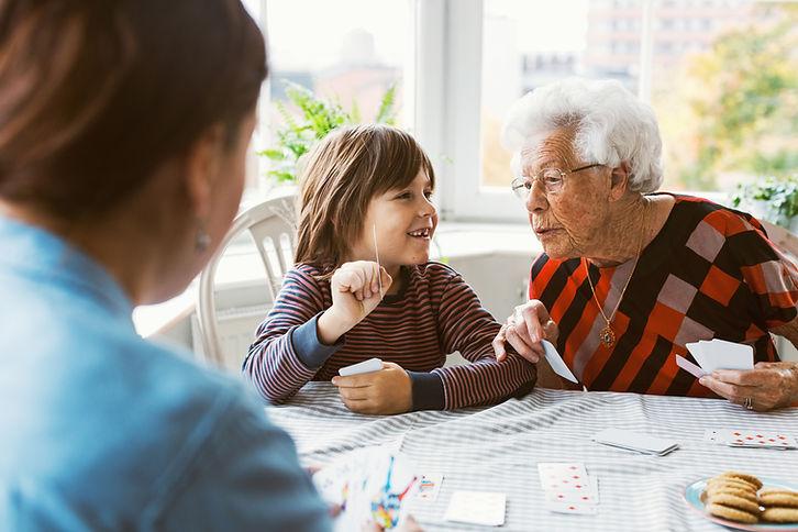 Ältere Frau spielt mit Enkel Karten