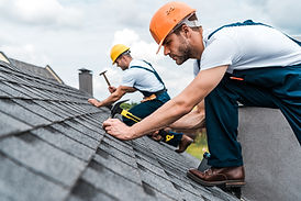 Roofer with orange helmet nailing a shingles with a hammer