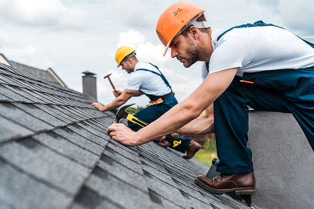 Roofers working. Both men are wearing orange and yellow hard hats and the man in the foreground is wearing a white t shirt and blue denim overalls.