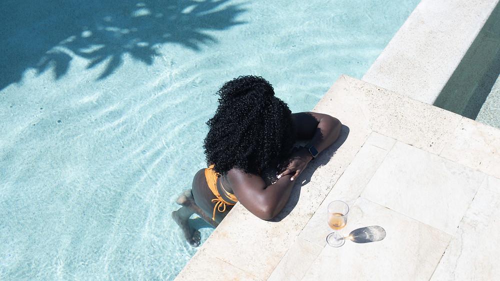 African-American woman in bikini relaxing in the pool