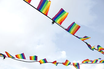 Pride flags hanging with globe lights in the sky.