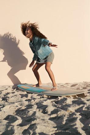 Fille posant sur la planche de surf