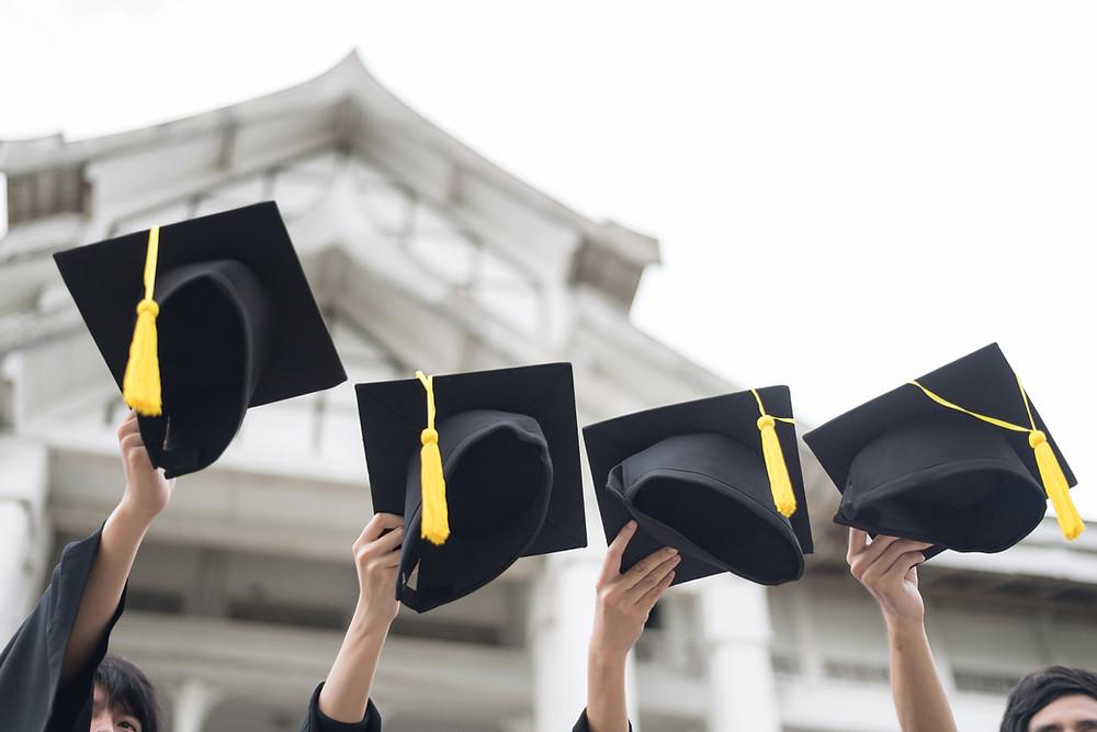 צילום של כובעים של בוגרי קולג' שהולכים לעוף באויר
