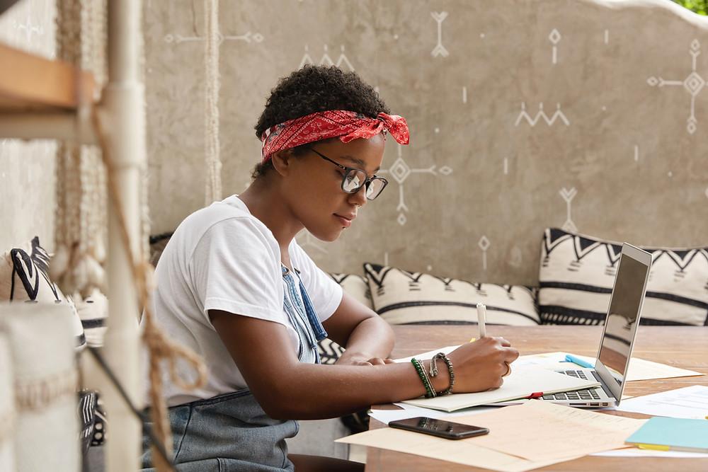 Uma jovem escreve em papel, em frente a um notebook