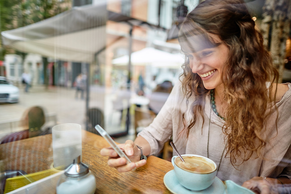 Happy young woman using smart application on her mobile phone
