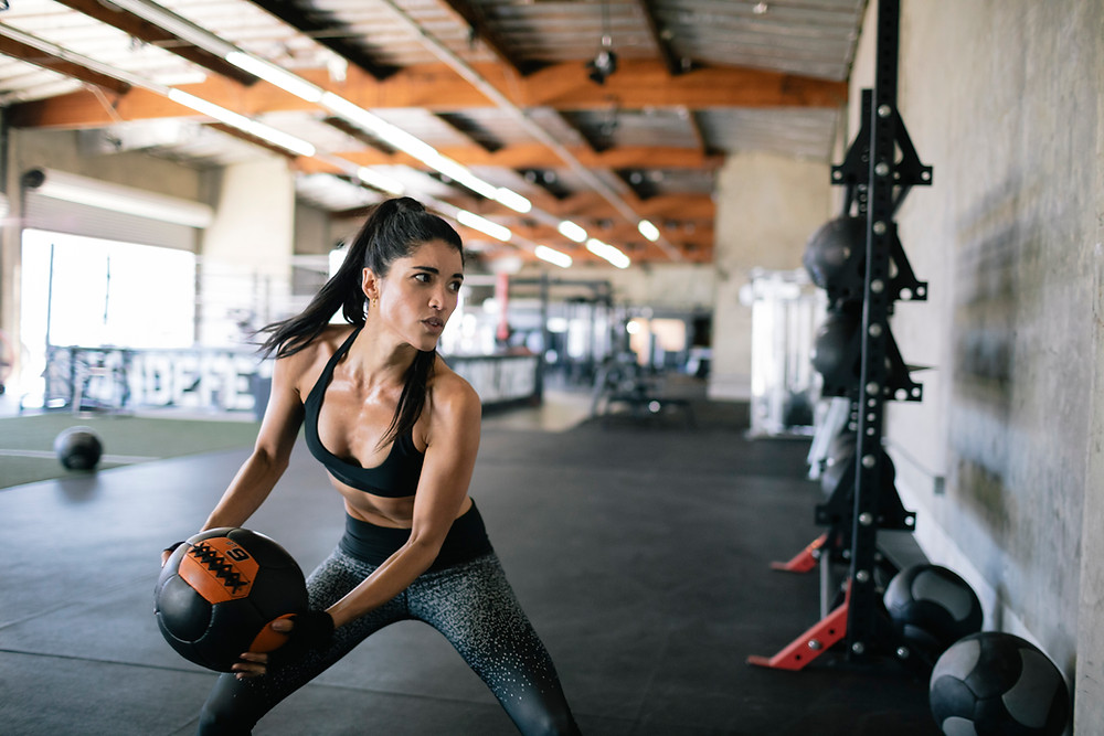woman in a gym throwing a medicine ball at the wall