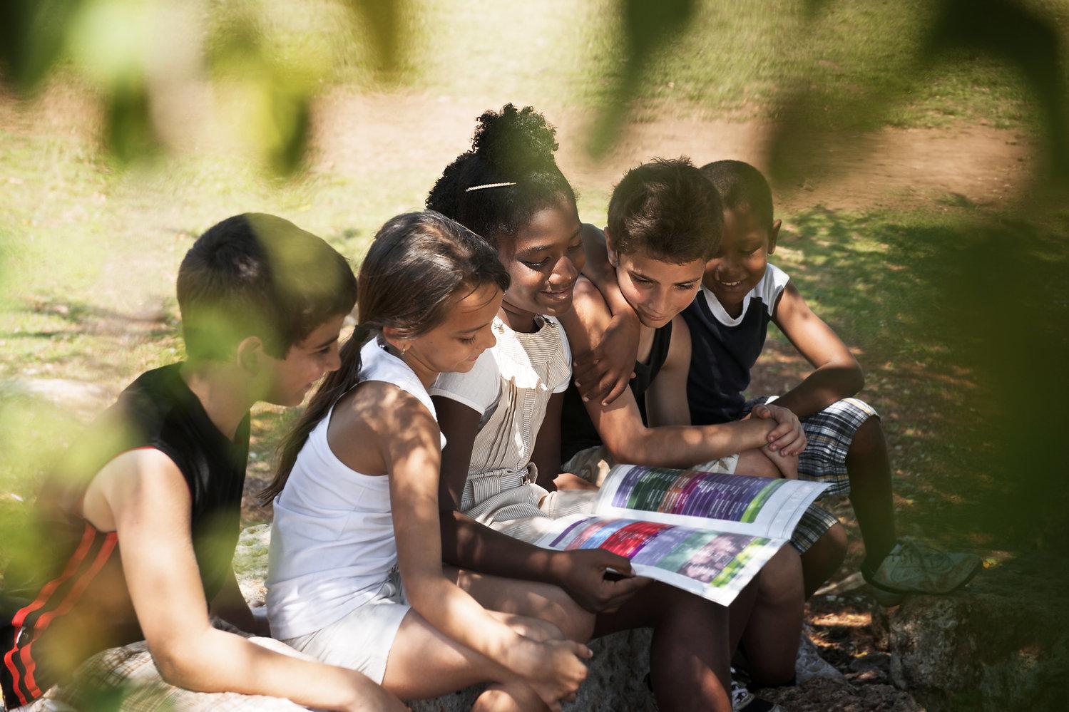 Kids Reading Book in Park