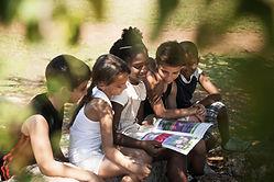 Crianças lendo livro no parque