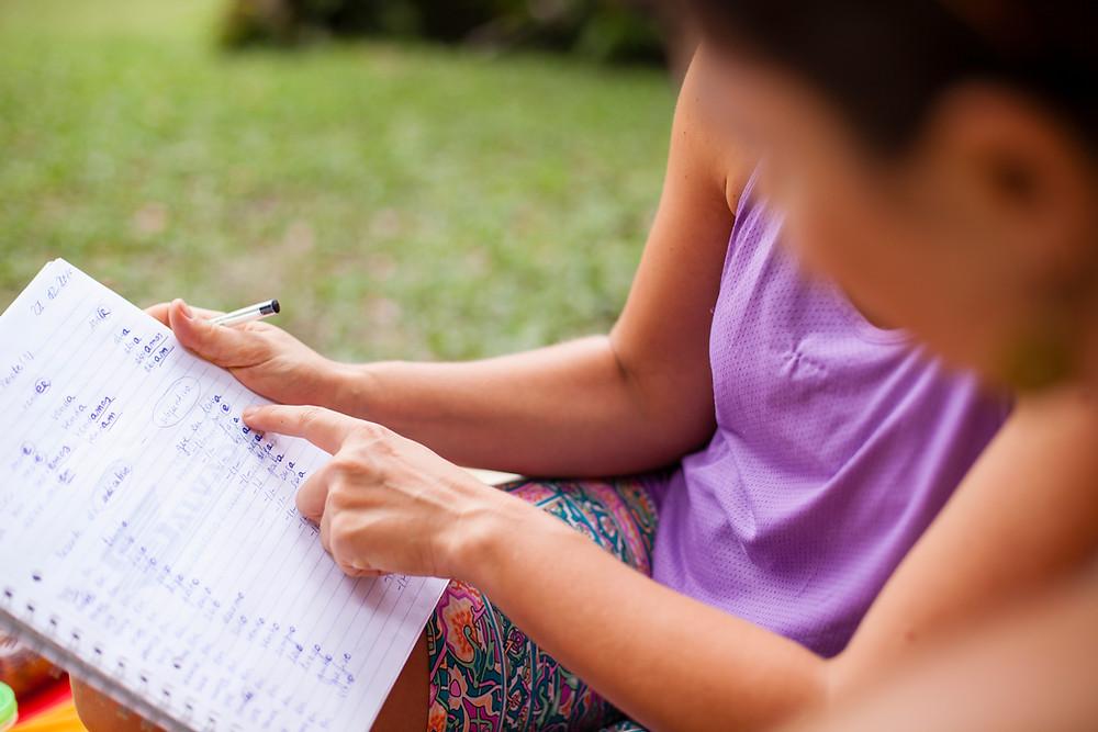 Em desfoque mulher e menino sentado em um gramado, ela segura um caderno e uma caneta preta e aponta para as anotações.