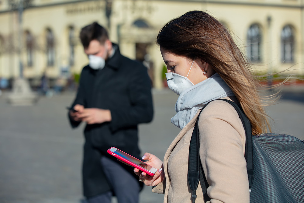 This is a picture of two people in an otherwise-empty city square, a man and a woman. Both are wearing masks and social distancing, and they're both looking at their phones.