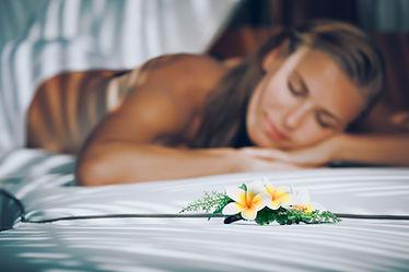 massage d'une femme allongée et fleur de frangipanier de polynésie