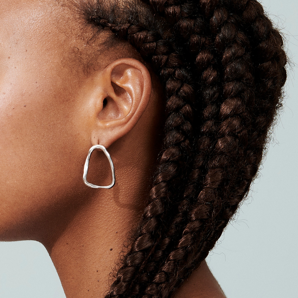 Profile of head. Only ear and back of head are visible. Person wears a silver triangular shaped earring and wears dark hair in long braids.