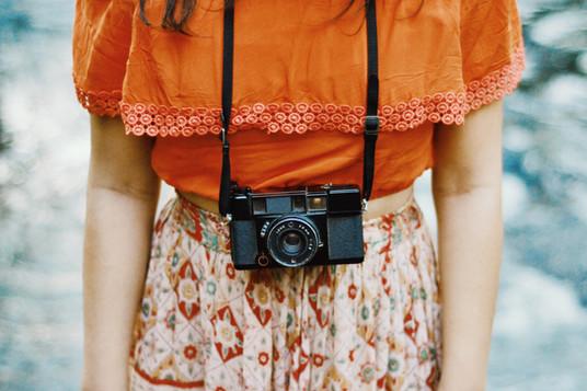 Mulher com câmera analógica