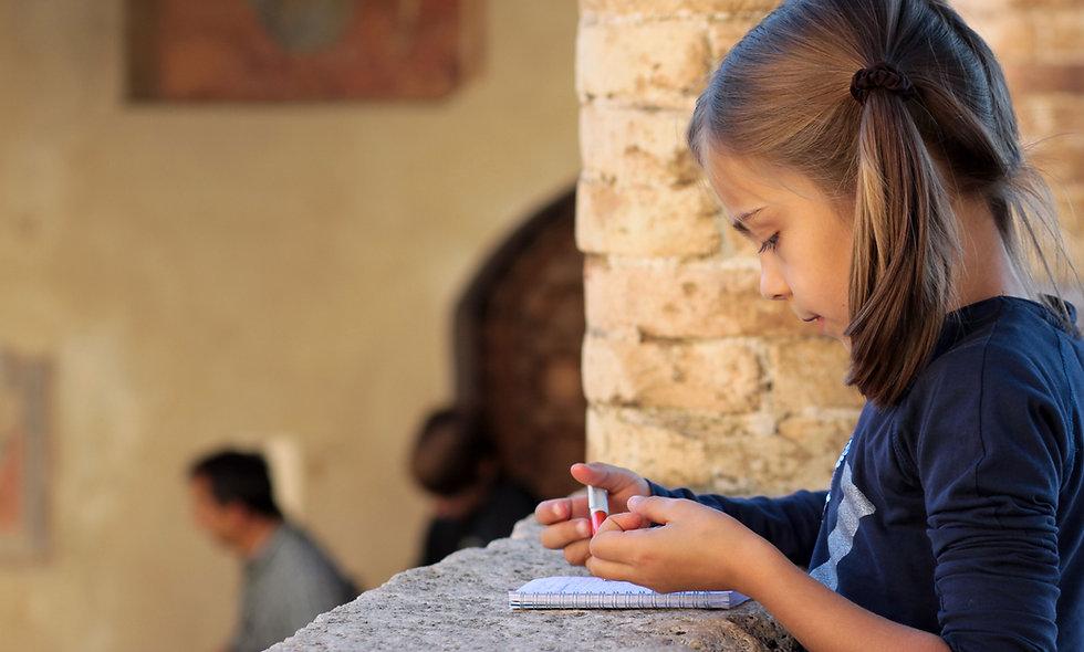 Girl writing in paper online homeschool programs online classes for kids language arts homeschool curriculum program language