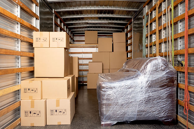 Interior moving truck with moving boxes stacked on both sides, blue overlay.