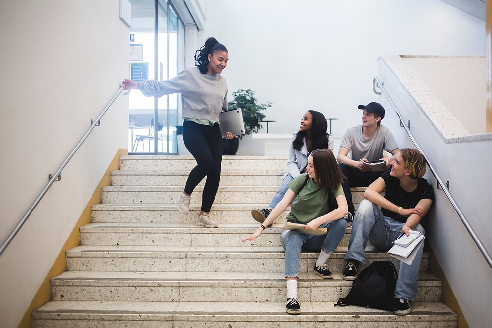 A student joining 4 other students sitting on a staircase