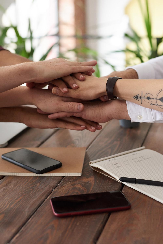 Equipe se cumprimentando sobre mesa de madeira com vários cadernos e smartphones