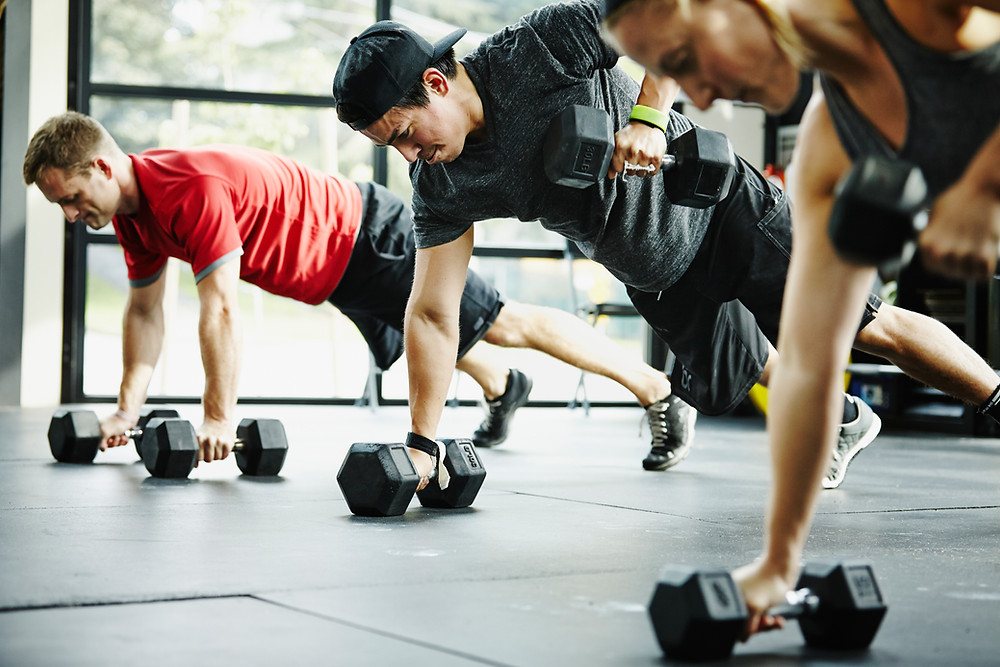 a group of trainers completing a CrossFit circuit with dumbbells