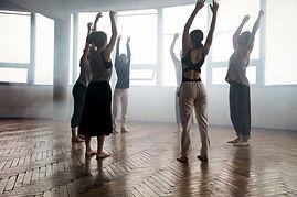 Séance de sophrologie en groupe. Mouvements d'étirements dans une salle dédiée à la pratique.