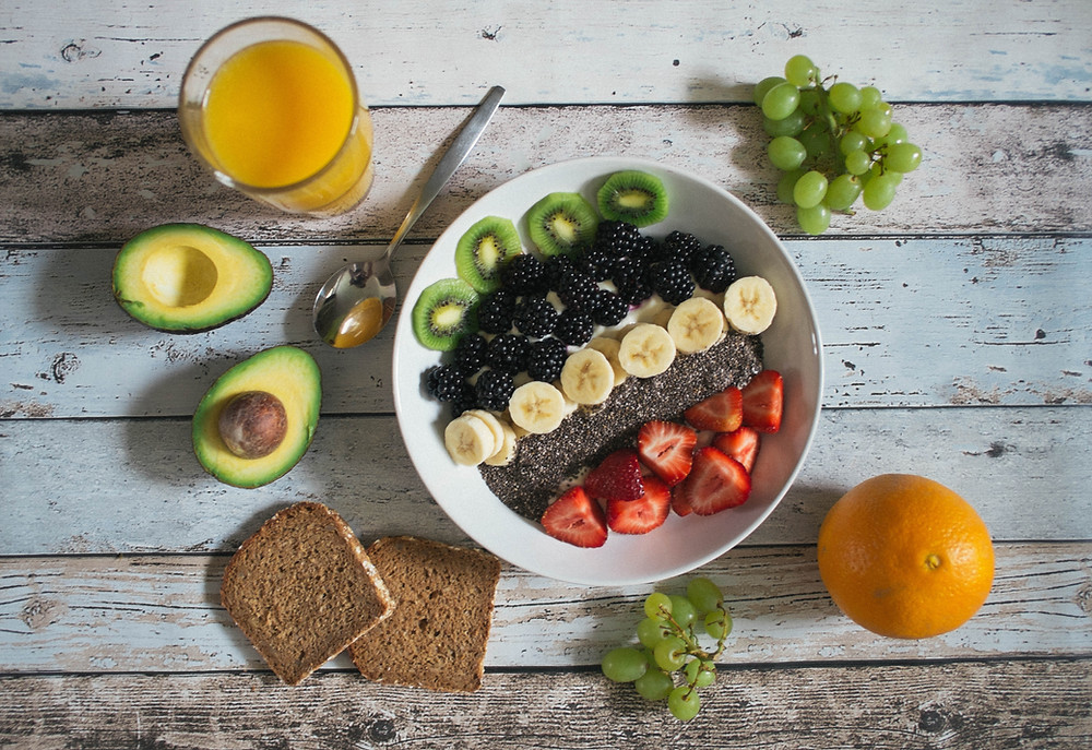 healthy breakfast with fruits, avocado and a smoothie bowl