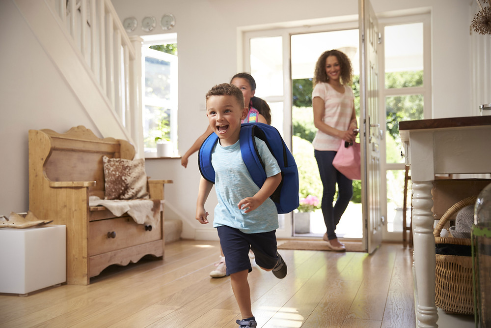 Kids getting inside their home after school with their nanny