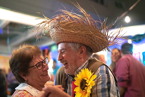 An older couple laughing with each other, hand in hand, dancing. The man has a grey beard and moustache and is wearing a blue checked shirt and brown leather waistcoat. He has a large, faux sunflower pinned to his shirt and an oversized straw sombrero on his head. The lady has short brown hair and is wearing glasses.