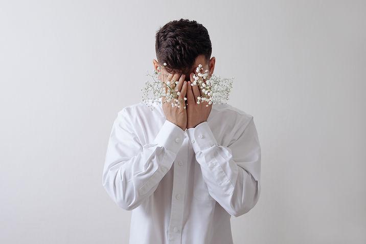 白い花を持つ男性モデル