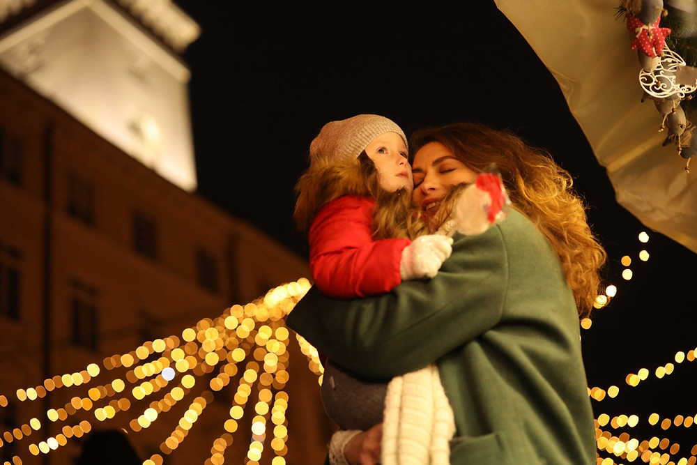 a woman holding her daughter outside while looking a Christmas lights