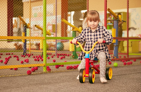 Chica montando un triciclo