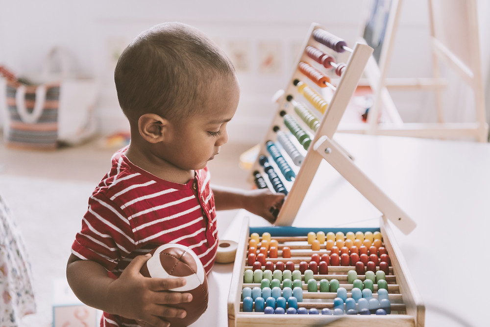 Black toddler in a red and white striped shirt playing with an abacus.