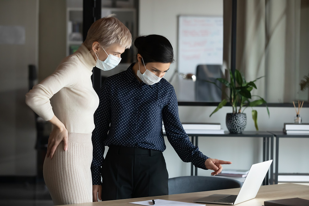 Two women in business attire wearing masks, standing at a conference room table and looking down at an open laptop.