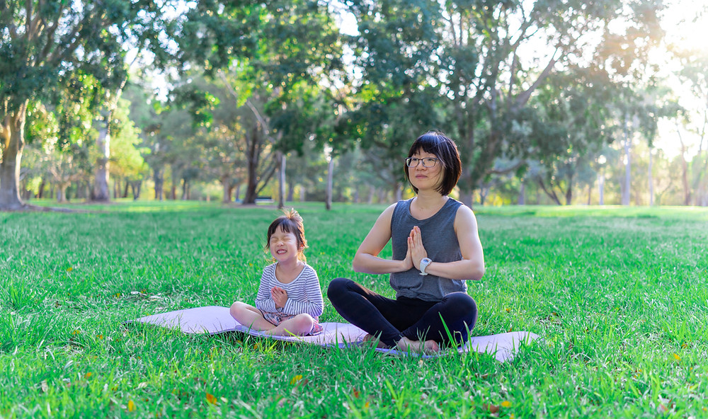 Asian Caregiver and child meditation outdoors