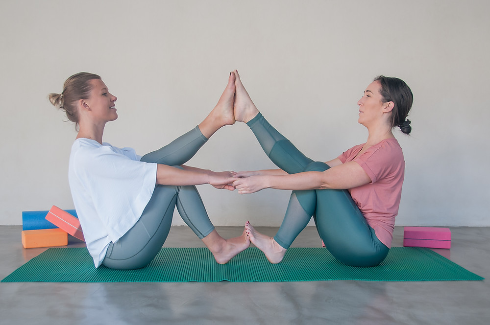 Two women taking part in partner yoga