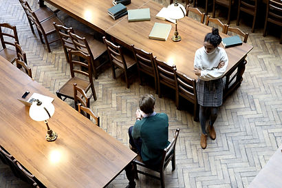 Global Journalism Innovation image - image of a library with two long wooden tables with wooden chairs