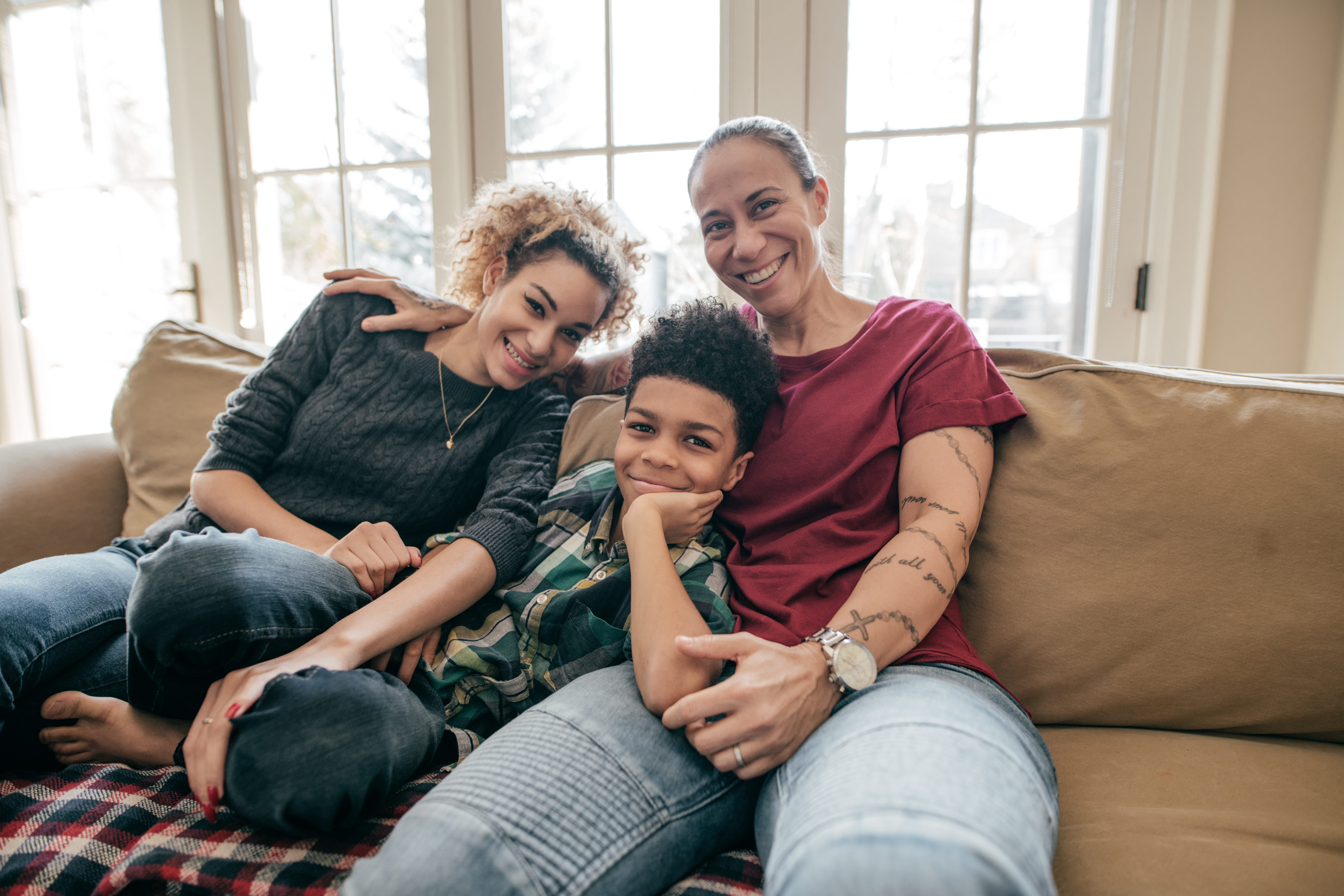A queer family pose together smiling on a couch in their home