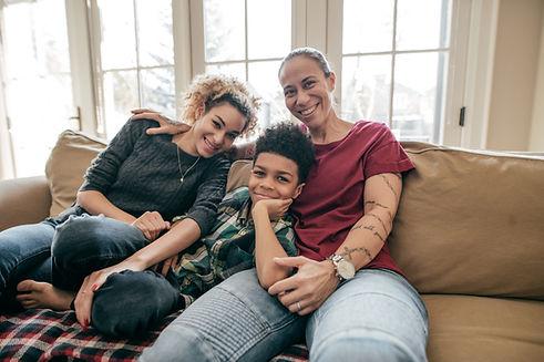 Une mère est assise sur un divan avec sa fille et son fils et nous regarde
