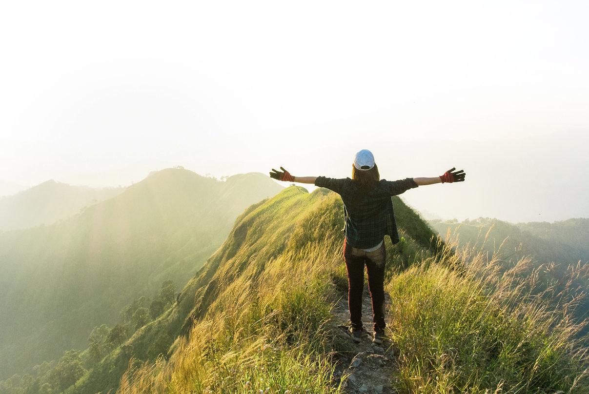 Profiter de la nature, femme ouvrant les bras en haut d'une montagne, Stage pleine nature, recentrer, se retrouver, prendre soin de soi, connexion, reconnexion, groupe, partage, rire, arbres, forêt, relaxer, intériorité, énergie, subtil, chakras