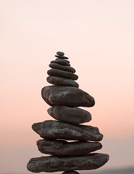 Various sizes of rocks blanced on top of each other against a peach sky