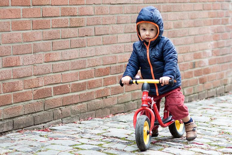 Kleinkind auf seinem Dreirad