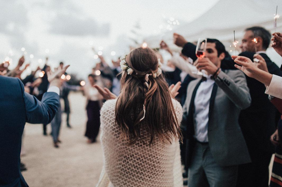 Das bild zeitgt eine Hochzeitsfeier, im Freien. Das Brautpaar ist dabei im Boho - Vintage Stil gekleidet und applaudiert zusammen mit ihren Hochzeitsgästen. Die Braut trägt dabei einen passenden Haarkranz. Die Hochzeitsgäste sind dabei im Hintergrund und tanzen und bejubeln das Brautpaar.