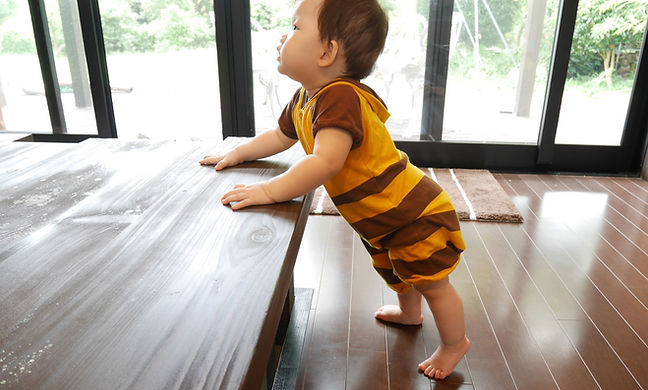 つかまり立ちの赤ちゃん