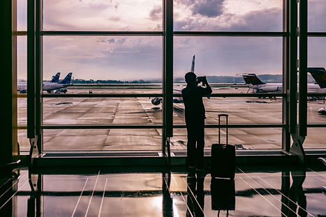 man-at-airport-taking-photo-of-planes-on-tarmac