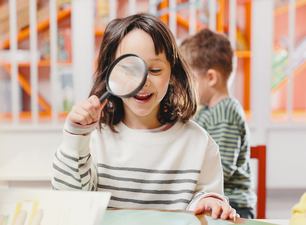 GIrl with magnifying class and Peninsula Family Coaching