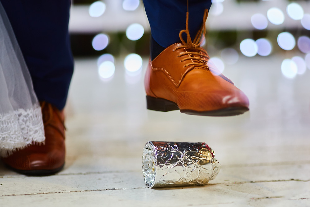 A foot hovering over a glass wrapped in tin foil at a Jewish wedding