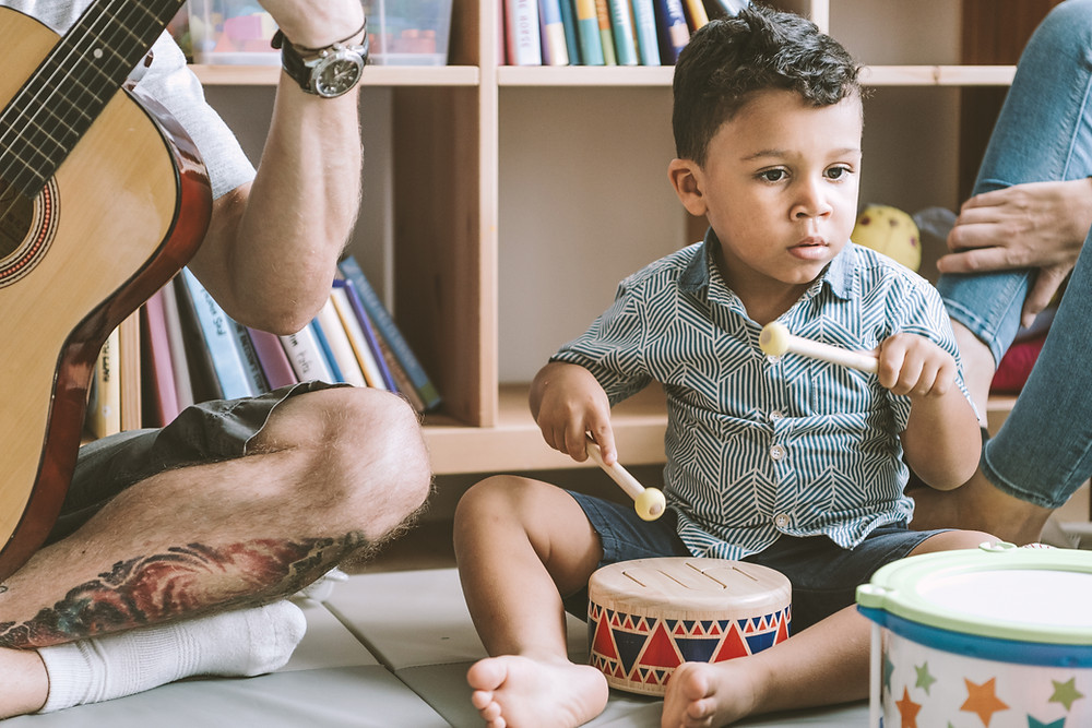 Young child playing a small drum, accompanied by a guitar