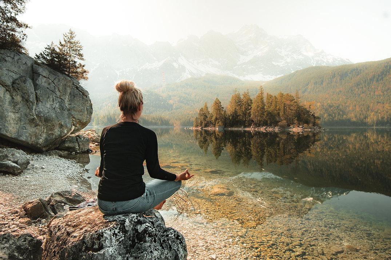 woman-meditating-by-side-of-lake a lake