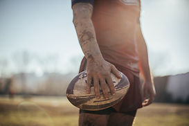A rugby player with stained clothes.